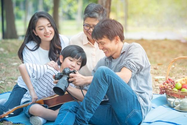 アジア家族の幸せな一緒に週末に余暇活動があります。幸せな家族の父は母親とおばあちゃんと息子にカメラショーを使用します。