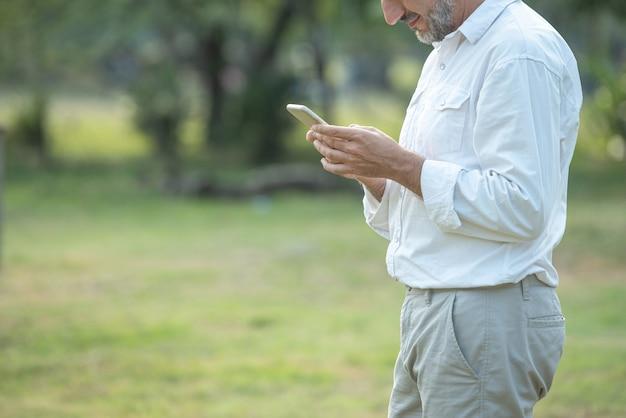 Кавказская средняя постаретая рука человека используя умный мобильный телефон и взгляд в телефоне пока текстовое сообщение в парке, концепции технологии беспроводной связи подвижности.