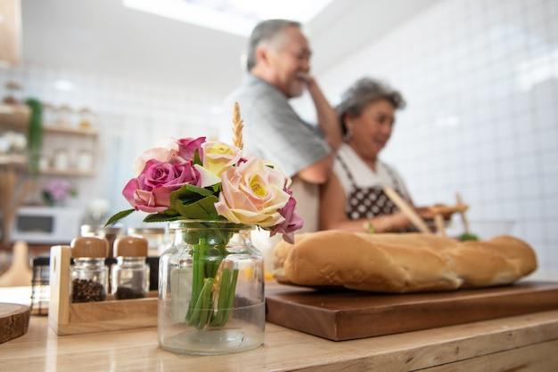 キッチンのテーブルの上のバラに焦点を当てたセレクティブディナーを調理する年配のシニアアジアカップル。愛はどこにでもあります。