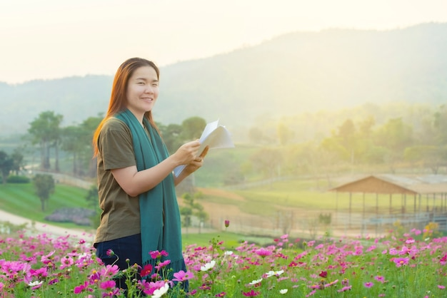 カジュアルドレスの手で幸せなアジアの女性は、コスモスフィールドに立って手でホワイトペーパーを保持します。