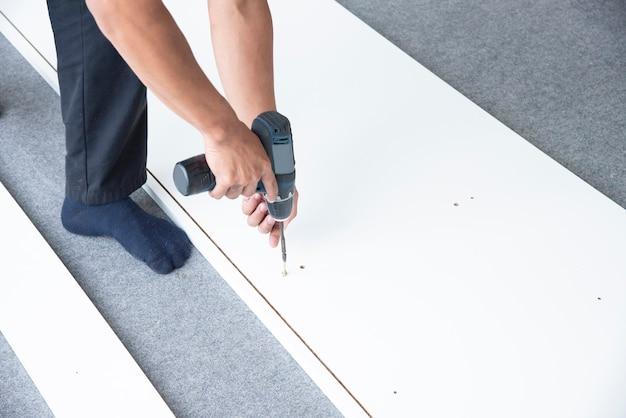 分割払いの家具の木板に手ドリルで働く男。