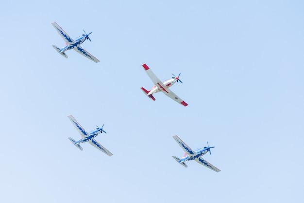 航空ショーのパフォーマンスで明るい青い空を背景に編隊飛行するスタント航空機