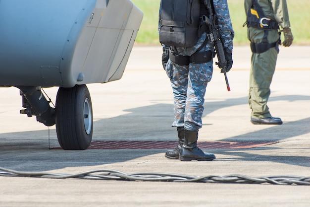 最前線に軍用ブーツとヘリコプターを備えた兵士の脚