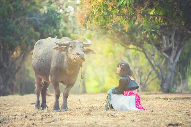 Остроумие девушки племени на колене с буйволом в поле.