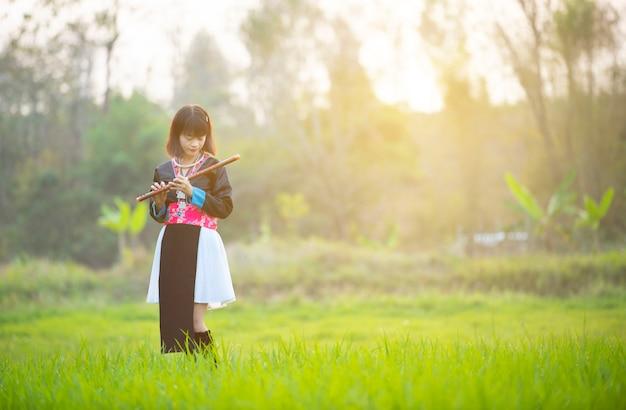 モンスーン期の田んぼを歩いて幸せそうな顔でカスタムドレス手で部族のアジアの女性の女の子はフルートを保持します。