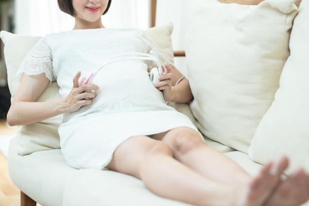 妊娠中のリラクゼーション。落ち着いた妊娠中の若いアジアの女の子音楽を聴く自宅でソファに横たわっている腹の近くにイヤホンを保持するお腹に取り付けられたヘッドフォンを使用して、胎児に良いモーツァルト効果を聞きます。
