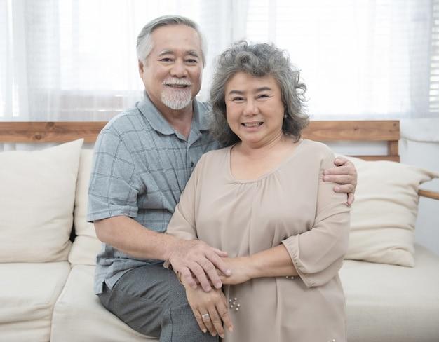 自宅で一緒に幸せな高齢者のシニアアジアカップル。祖父と祖母は、自宅の居間でコーチに座り、退職後のライフスタイルで余暇を過ごします。