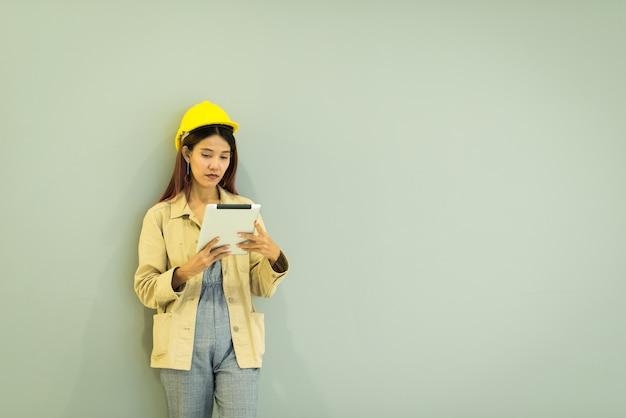 ハードな帽子の女性工業医のアジア人女性の成功は、タブレットスマートフォンを使用しています