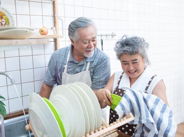 自宅の台所で自宅の流しで皿を洗って幸せなアジアの年配のシニアカップル。