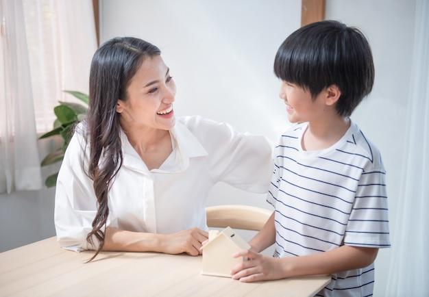 Азиатская монетка руки сына на ладони матери с контейнером формы дома сбережений, мама семьи счастья и ребенок инвестируют для финансов планирования образования в гостиной дома.