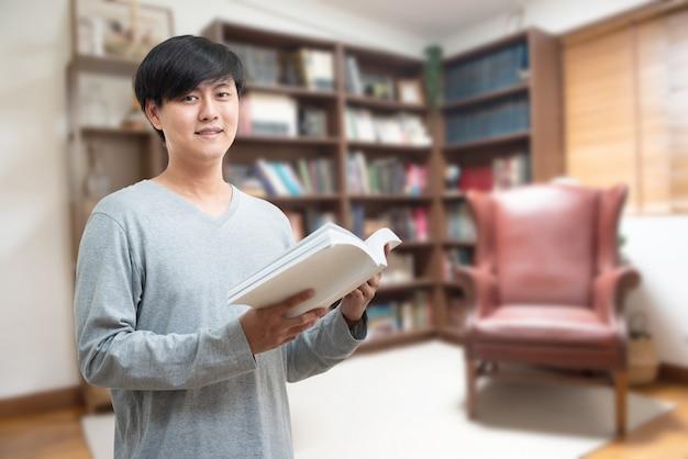 世界本の日の概念。若いアジア人大学生は、教育研究と自己改善のための大学図書館の本棚に座って本を読んでいます。奨学金と教育の機会。