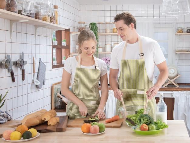Счастливая кавказская семья пар варя в современной кухне дома с влюбленностью. женат романтический мужчина и женщина, приготовление салат из свежих овощей. концепция здорового образа жизни.