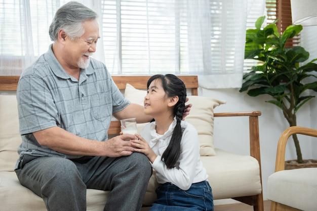 幸せなアジアシニア高齢者祖父は孫の世話をし、自宅のソファー、退職健康ライフスタイルコンセプトに座っている間、ミルクと頬にキスを与えることで世話をします。