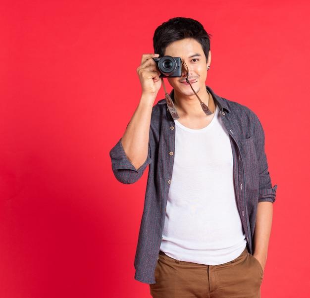 若い男のファッションはカメラのドレスのカジュアルな旅行を使用します