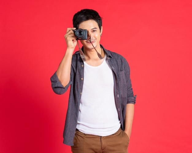 若い男のファッションは、カジュアルな服でカメラを使用します。旅行のコンセプト