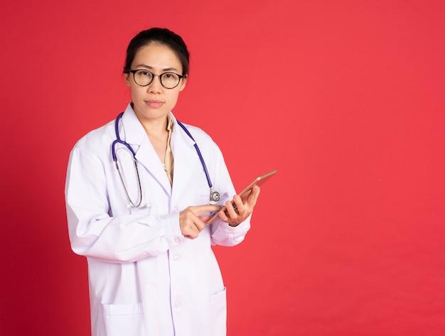 Азиатский доктор женщины используя таблетку на красной стене