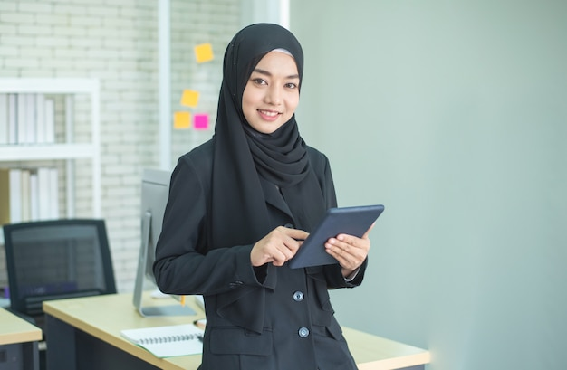 Мусульманская работа молодой женщины в офисе используя телефон