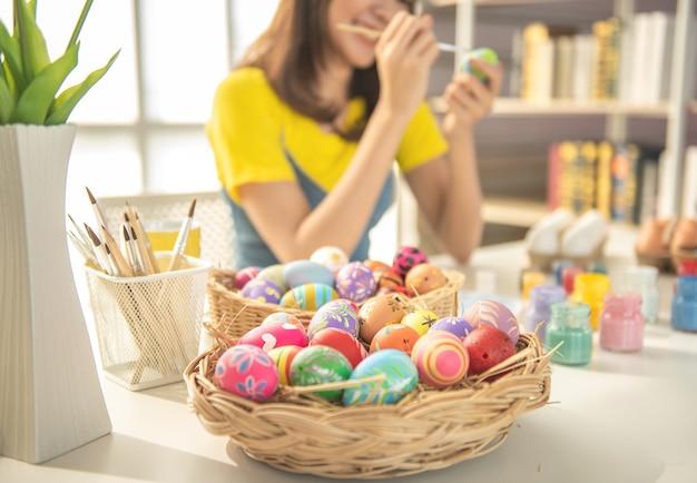 Молодая красивая девушка рисует цвет на пасхальное яйцо