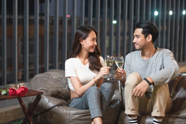 アジアのカップルのトーストワインはナイトクラブで祝う