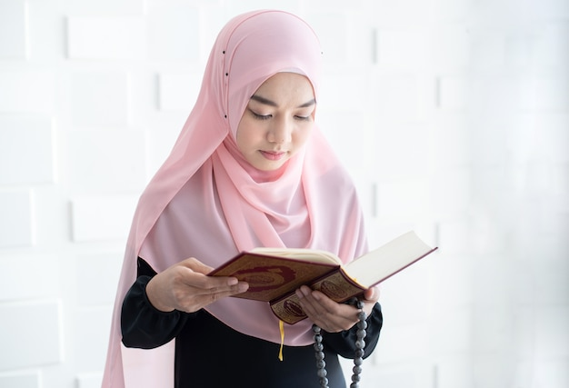 コーランを読んで美しい若いアジアのイスラム教徒の女性