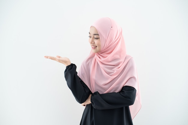 ビジネスの服装と混合ポーズと灰色の壁に分離されたジェスチャーでヒジャーブを着ているアジアの美しいイスラム教徒の若い女性の半分の長さの肖像画。テクノロジー、ビジネスファイナンスのテーマに適しています。