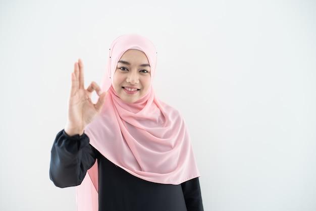 Половинный портрет длины одежды и хиджаба азиатской красивой мусульманской молодой женщины нося при смешанные представления и жесты изолированные на серой стене. подходит для технологии, тема финансирования бизнеса.