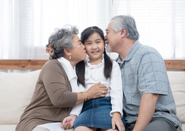 Счастливые азиатские бабушки и дедушки, сидя на диване у себя дома играть и целовать в щеку маленькой внучки