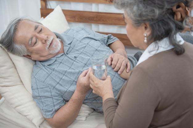 コピースペースと自宅のソファ、健康と医学の概念に横たわっている間薬と水を飲んでアジアのシニア男性。