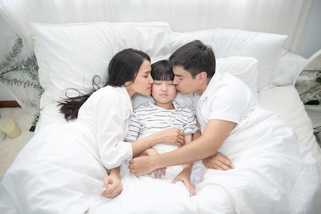 若いアジアの母、父と少年がベッドで寝ている、ママとパパが息子の頬にキス、上からの眺め