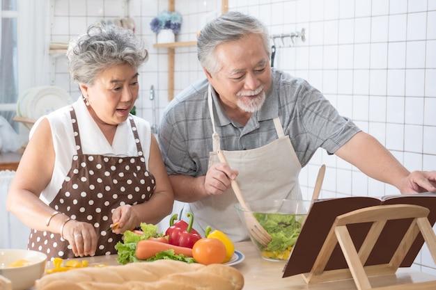 Пожилая пара читает кулинарную книгу приготовления пищи на кухне