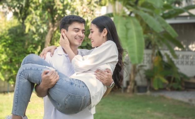 若いアジアの幸せな愛情のあるカップルは公園で楽しい時を過します。ボーイフレンドは彼のガールフレンドを腕の中で運ぶ。
