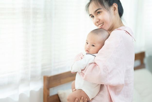 家族、子供、親のコンセプト-自宅で彼女の腕の中で生まれたばかりの赤ちゃんを抱いて抱いて笑って幸せな美しい若いアジアの母。