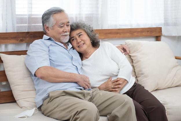 自宅で一緒に幸せな高齢者の上級アジアカップルの肖像画。