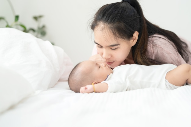 ベッドの上の生まれたばかりの赤ちゃんにキス美しい若いアジアの母を閉じます。ヘルスケアと医療。アジアの女の子のライフスタイルが大好きです。