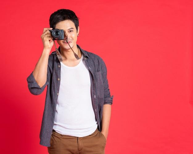 若い男のファッションはカジュアルな服の旅行でカメラを使用します。