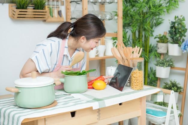 Счастливая азиатская женщина смотря рецепт на кухне