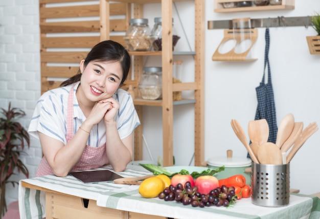 Счастливая азиатская женщина делая рецепт на кухне