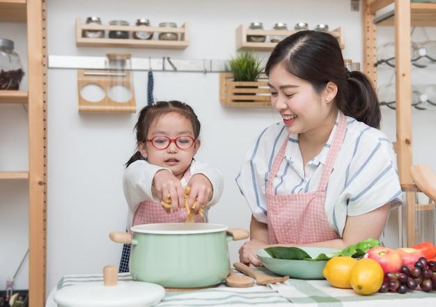 台所で娘や妹のために料理する方法を教える若いアジアの母。