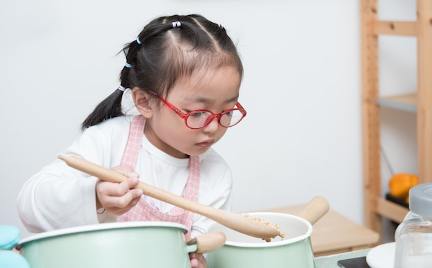 Азиатская маленькая девочка, смешай соевые бобы в кастрюле и играй на всех кулинарных блюдах на кухне, готовит еду или десерт и пробует все дома.