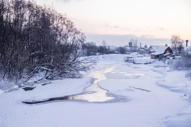 冬の小さな川。冬の風景。川の水。冬の木。雪。