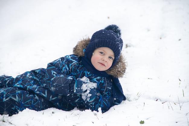冬の雪の中に小さな男の子があります。子供と一緒に歩きます。冬の散歩。白い雪。公園の雪