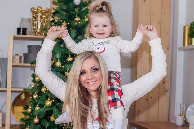 クリスマスツリーの横にある母と娘。休日の新年とクリスマス。美しいママと娘。