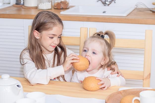 Две сестры за столом едят хлеб. легкая закуска. девочки едят. яркая кухня.
