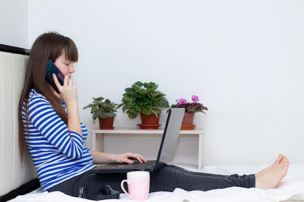 Беременная девушка с ноутбуком на кровати.
