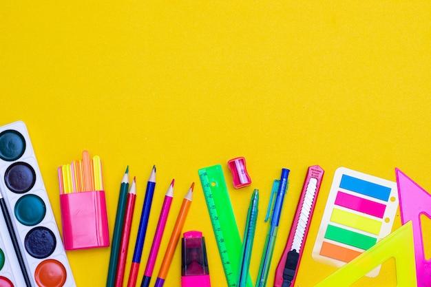 黄色の背景に事務用品。明るい黄色のテーブルにさまざまな学用品。学校のレイアウト。