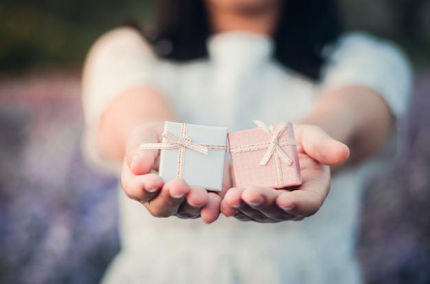 Девочка держит маленькие подарочные коробки