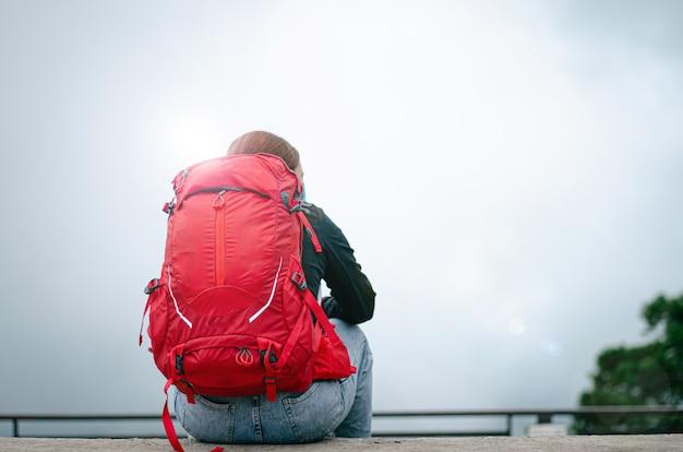 バックパックを持って旅行する女性。座ってリラックスして、涼しくて美しい自然を眺めています。