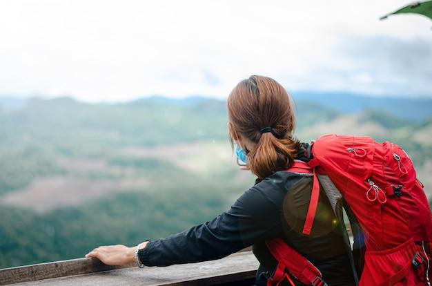 バックパックを持って旅行する女性は、美しい自然を眺めながら楽しんでいます。それは彼女の休日です