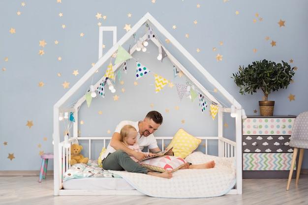 Прелестная маленькая девочка и ее молодой папа читают книгу пока сидящ в украшенной кровати дома на спальне. интерьер детской комнаты