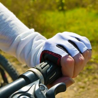 Рука держа ручку бар. женщина катается на велосипеде в парке